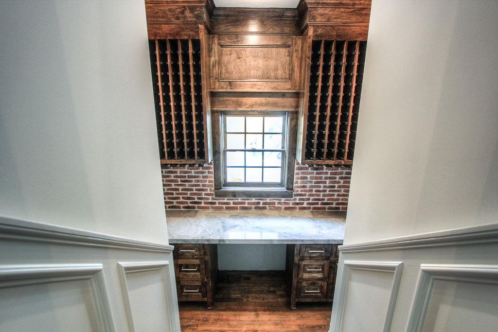 The sunken wine room fully equipped with storage and wine refrigerator. Reclaimed brick backsplash, stained wood cabinets and quartzite counter make this a surprisingly intricate space.