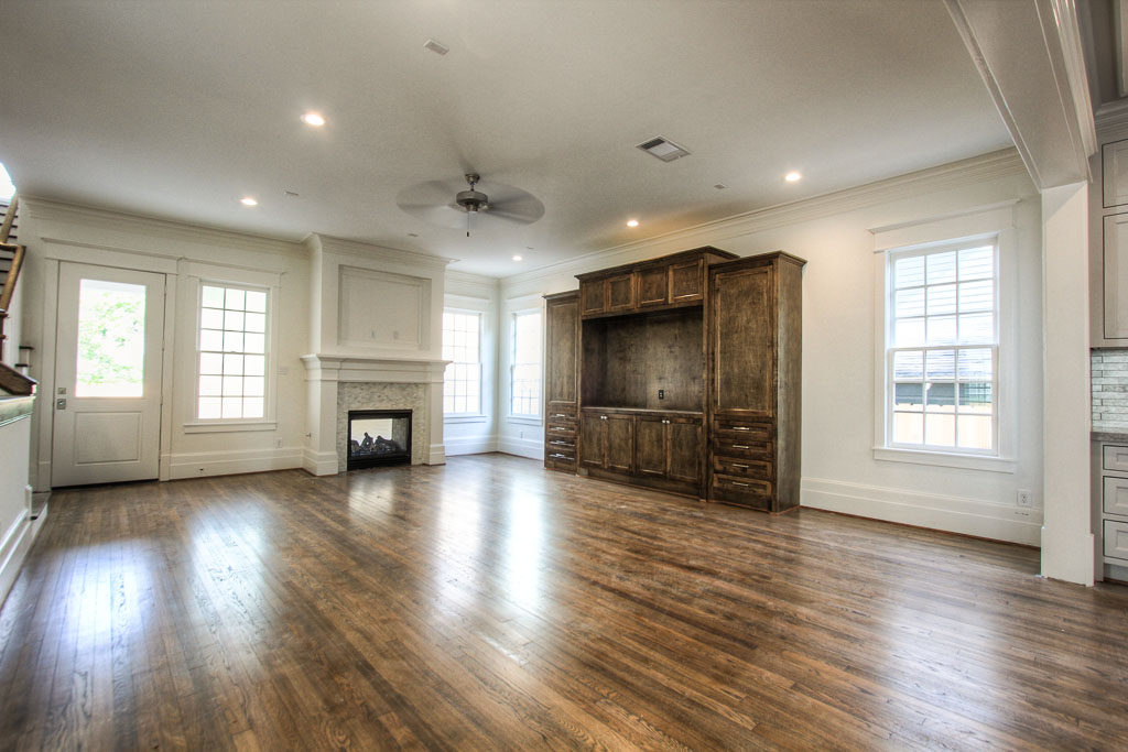 Spacious living room with fireplace, ten foot ceiling, double crown molding, wood floor and a great view of the backyard.