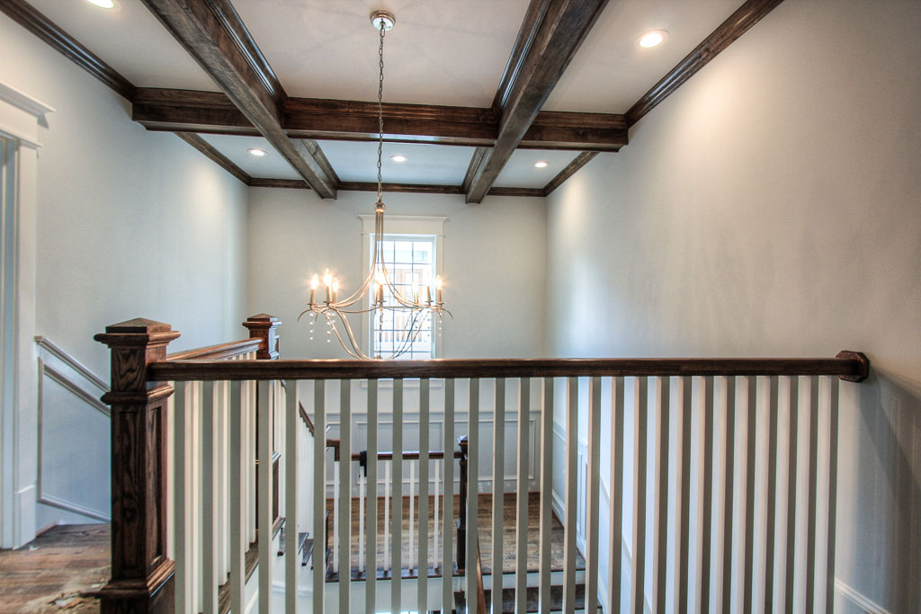 The wide staircase opens up to a spacious second floor landing for ease and accessibility to the three auxiliary bedrooms, as well as a hallway leading to the tranquil master suite. Again, richly stained beams grace the high ceiling.