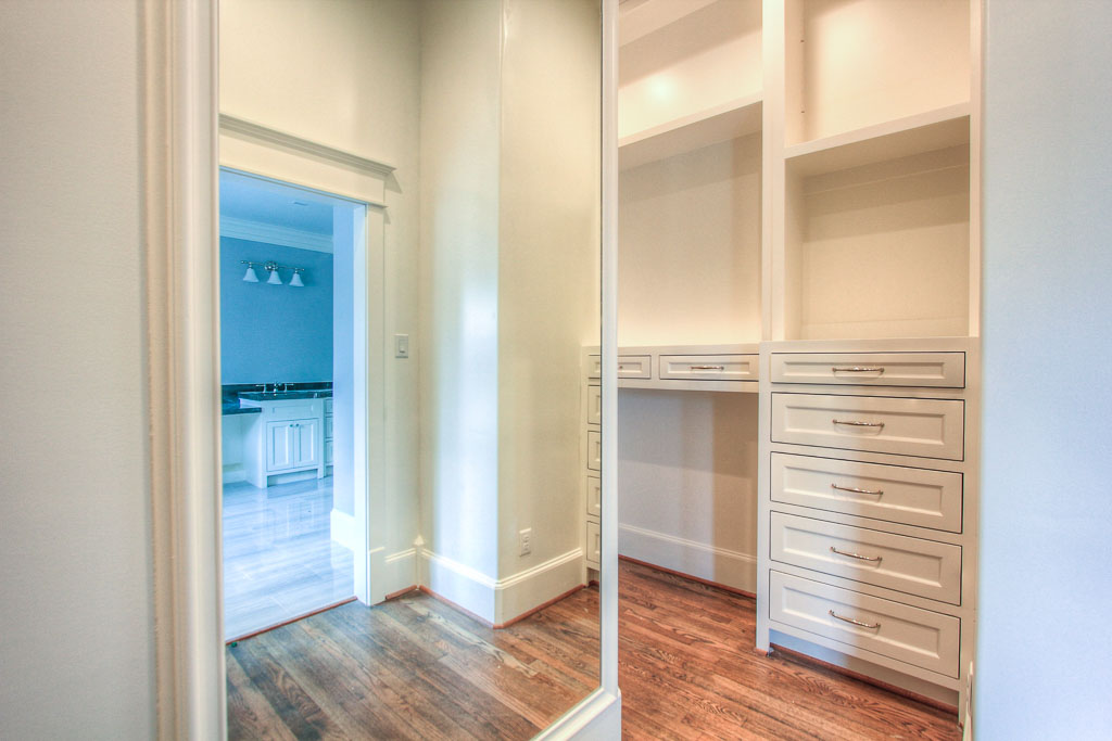 Large closet off of master bathroom with custom built-in storage and floor-to-ceiling mirror that divides the space into two functional areas. You really must see in person to fully appreciate its size and functionality.