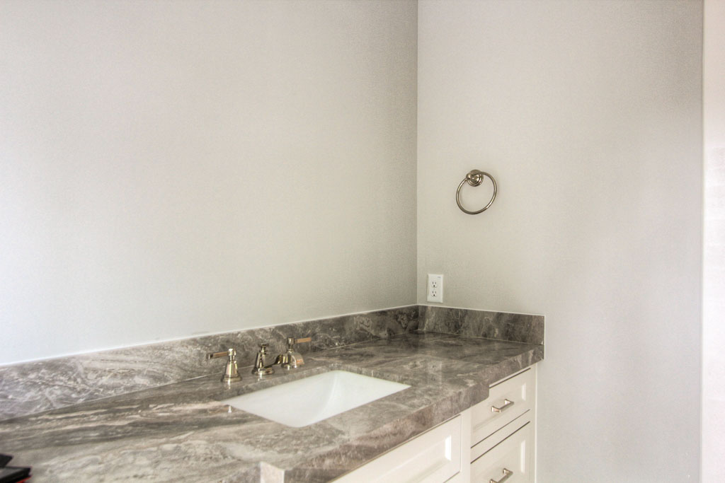 Bathroom cabinets providing lots of storage. Granite counter tops and classic subway tile.