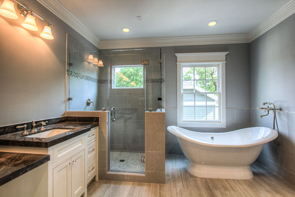 Master bathroom with freestanding tub, and hue shower with textured tile walls and stone flooring. Dark marble counters and smokey gray walls create a nice contrast of this suite from the remainder of the home.