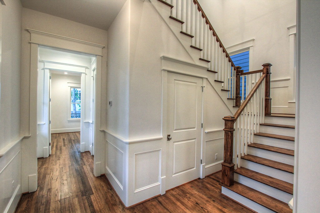The entrance and landing at Allston showcase several signature features of Smith Family Homes, including wood paneling details, reclaimed hardwoods, and heavy custom casing on doorways and windows, true to their Acadian influence.