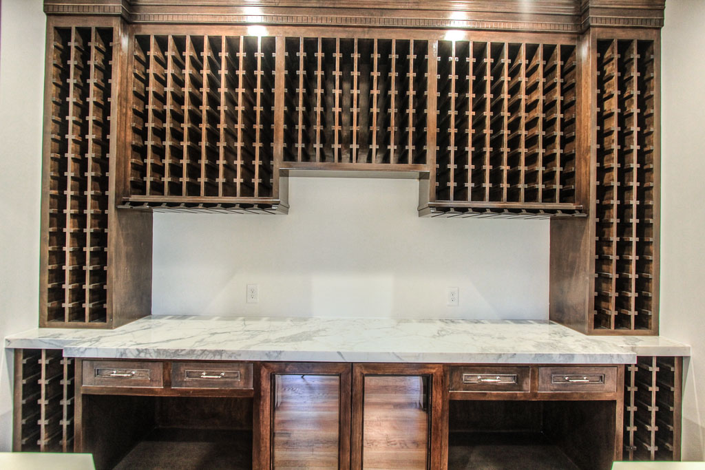 Wine room immediately off dining once again features Calacatta gold counters and is fully equipped with storage and cooled wine storage. Rich, stain creates a dramatic view for guests. The pass-through windows maximize entertaining space.