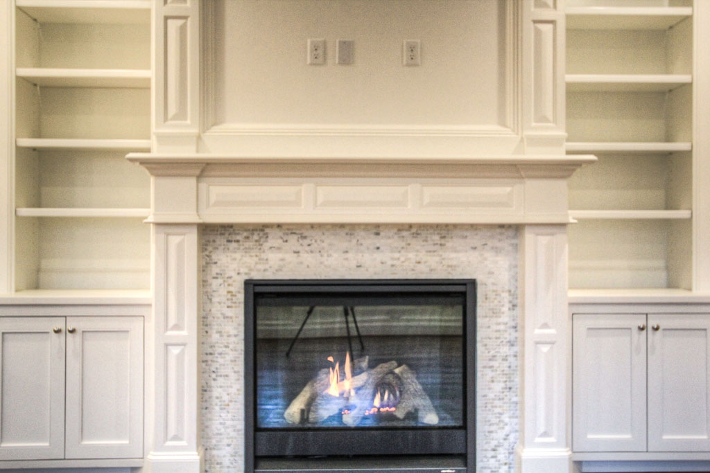 The living area downstairs has built-in window seating and a fireplace surrounded by shelving and marble tiles.