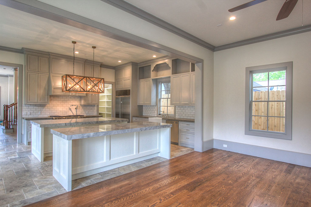 Kitchen w/ dual Super White Quartz islands will be the heart of the home, w/ island seating adjacent to great room. Walker Zanger tile. Rustic and refined is a noticeable theme: Versailles pattern Travertine, wide-plank hardwood, limestone counters.