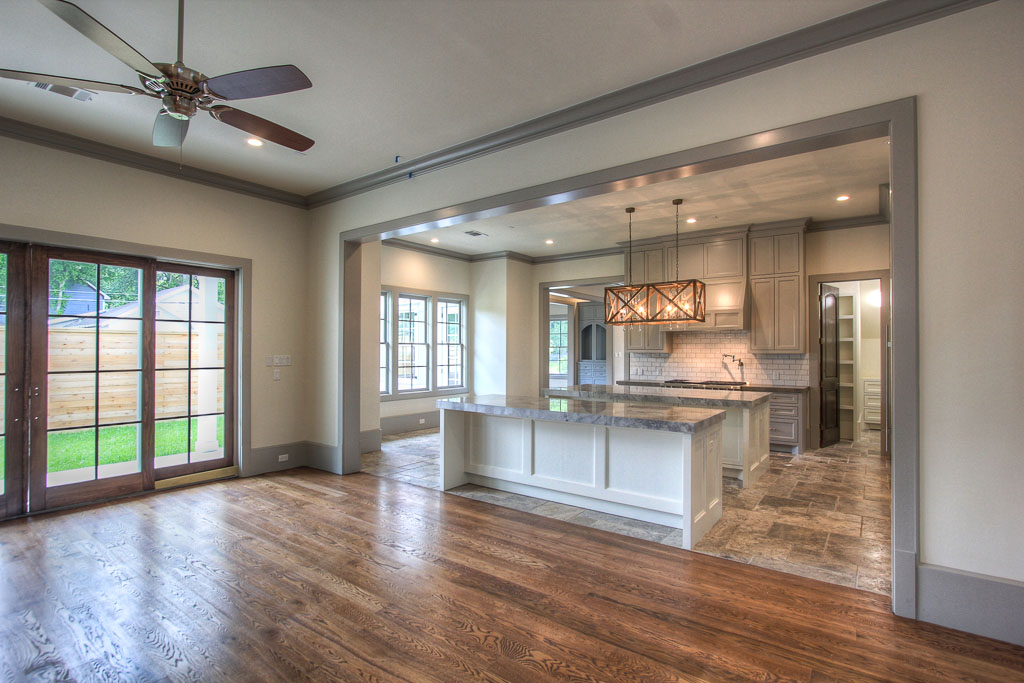 The kitchen opens to a grand great room flooded with light from huge windows and a door to the fully fenced, private front yard.