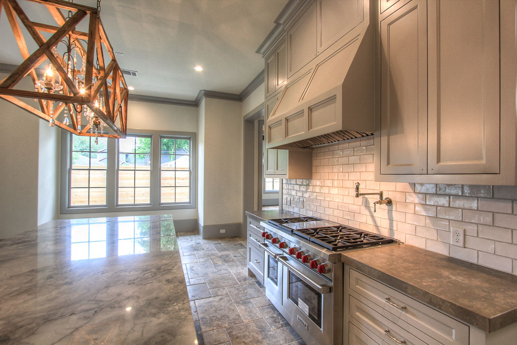 """Walker Zanger tile backsplash, 48"""" Wolf chef's range with double oven and convenient potfiller. 48"""" Sub Zero refrigerator. Lagos Azul limestone countertops continue the mix of natural textures."""