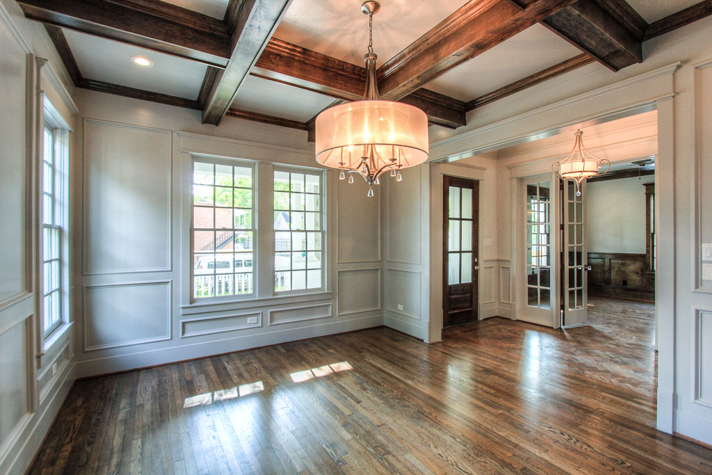 The large formal dining off the foyer showcases the builder's signature millwork and finishes: floor-to-ceiling wood paneling, coffered ceiling with stained beams, designer lighting, and enameled walls & ceiling give a rich refined depth to the space.