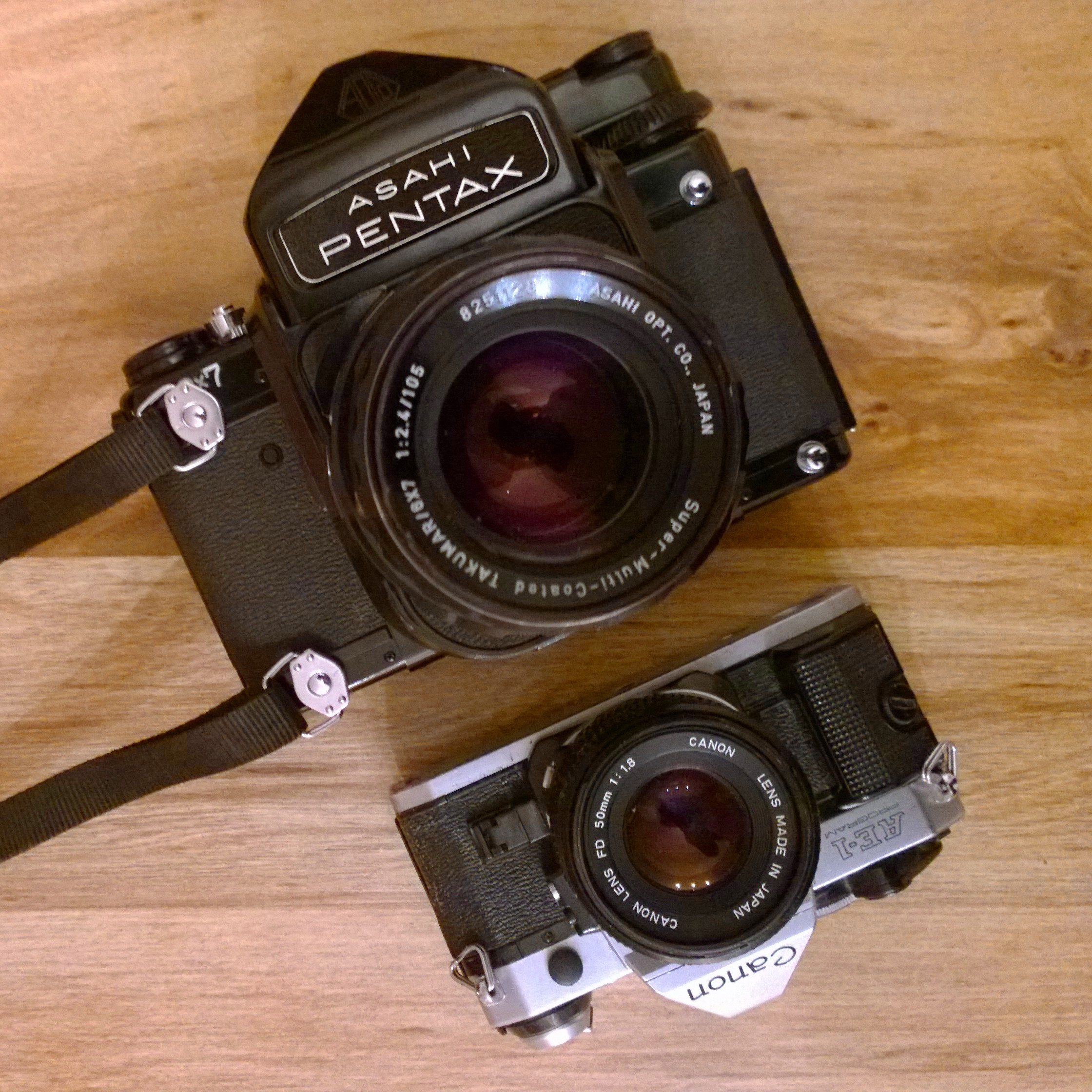 The Pentax 6x7 compared to a 35mm Canon AE-1, both shown with standard lenses.