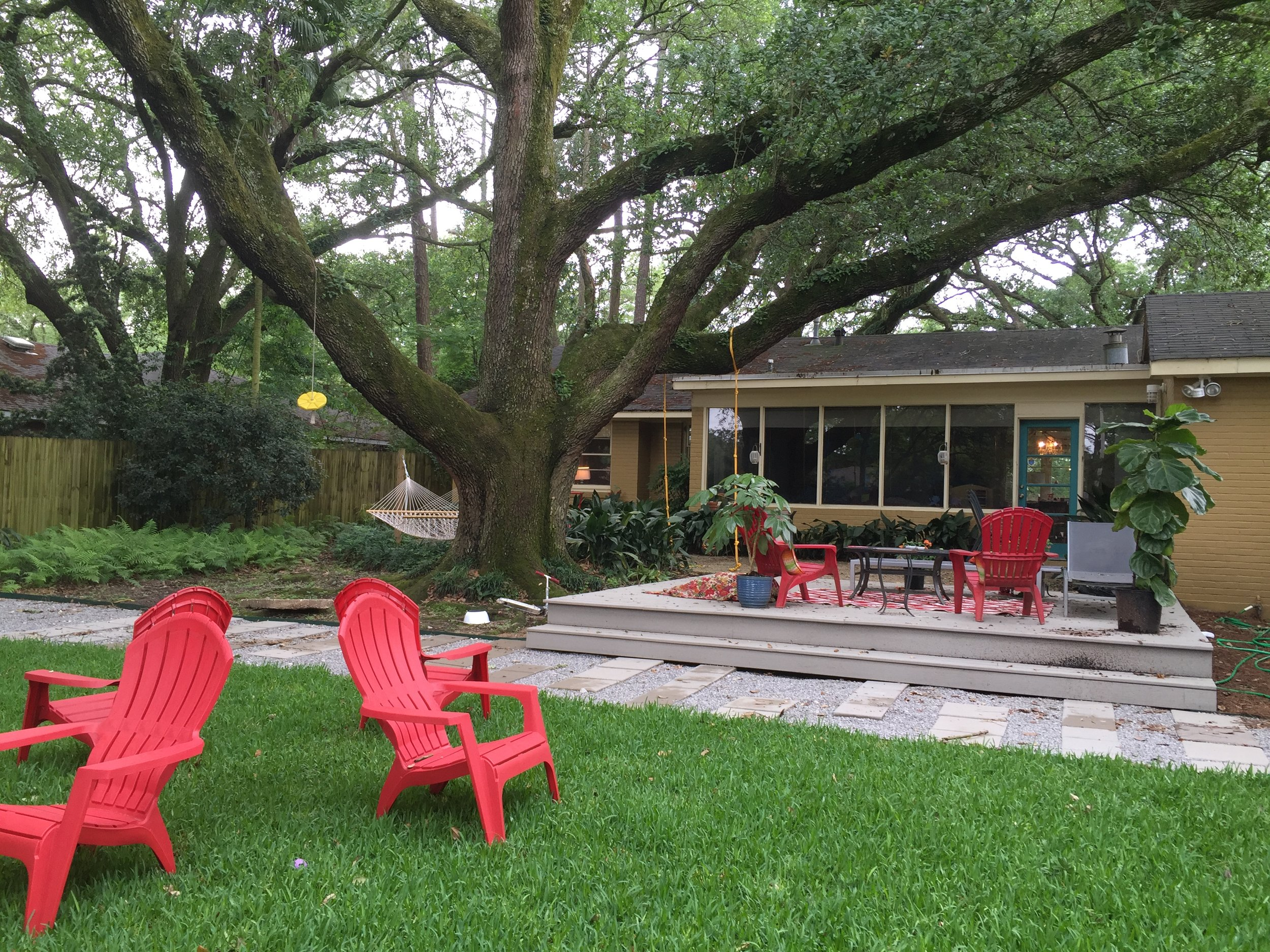 the back yard showcases the large oak tree and plenty of seating areas for the family.