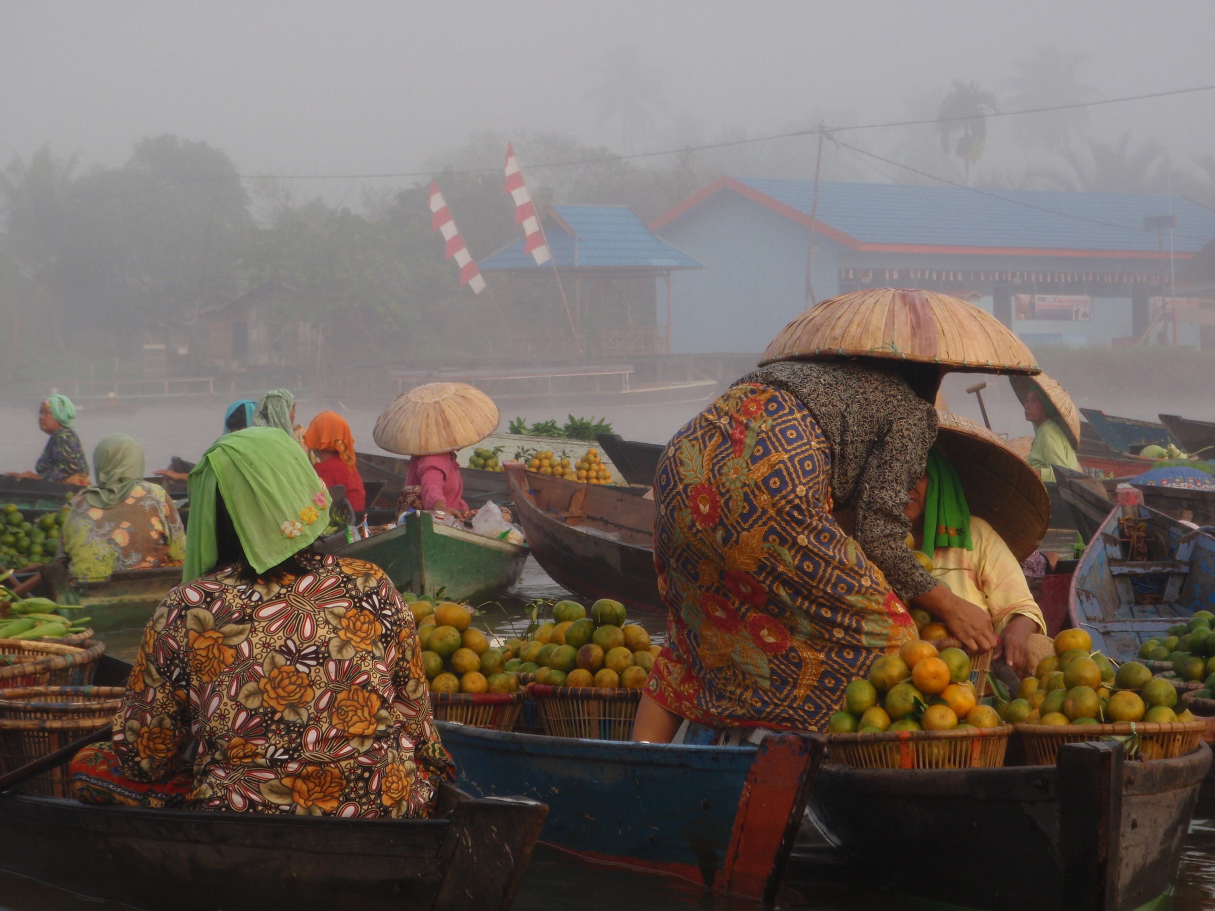 A moment of color at the floating markets of banjarmasin, an industrial city in the jungle of borneo, indonesia