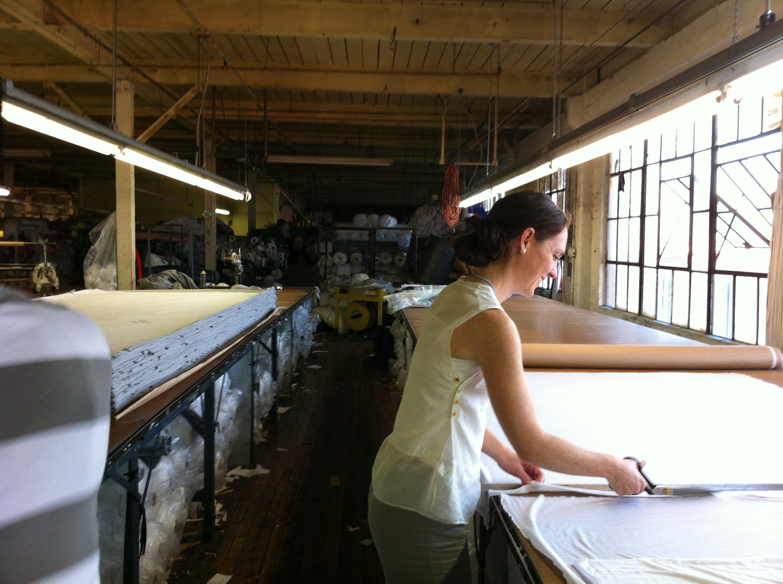 rachel doing her part by cutting fabric from the roll in preparation for pattern application