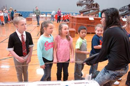 North Lamar High School art student Megan Grogan assists with the dinosaur exhibit by holding a large tooth so those touring can get a closer look. Inquiring as to what prehistoric animal the tooth belonged to are North Lamar elementary students Savannah Pickering, Berkley Smith, Grace Maddox, Luis Morales and Ryan Stanley.