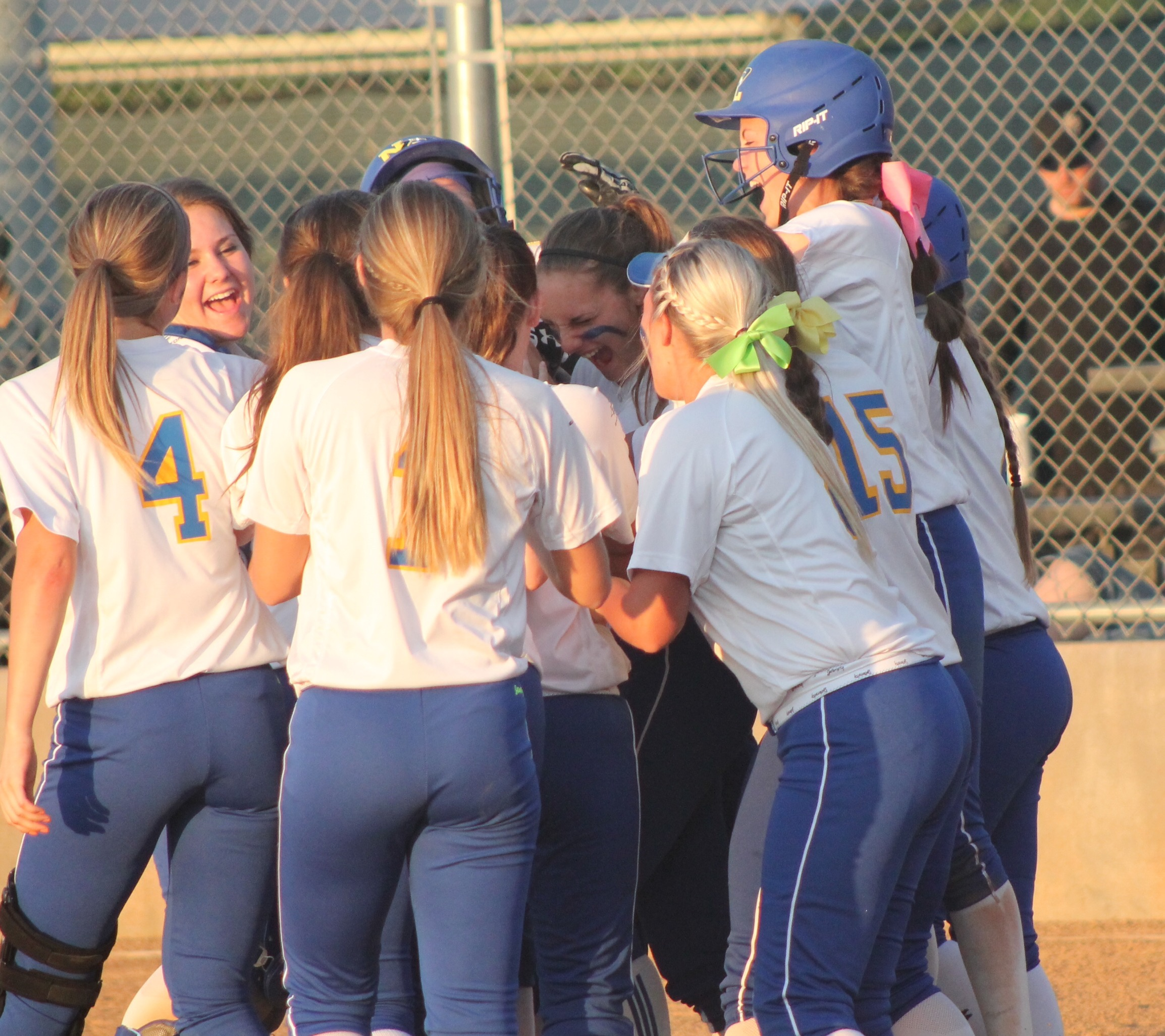 Pantherettes surround Erin Scholl as she reaches home plate after a three-run homer.