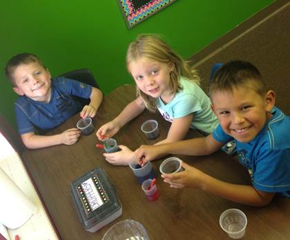 Higgins Elementary first grade students Brenton Upchurch, Sarah Chrisman, and Josiah Bond work on an experiment in science class. Kindergarten and first grade students at Higgins change classes during the day for their subject areas.