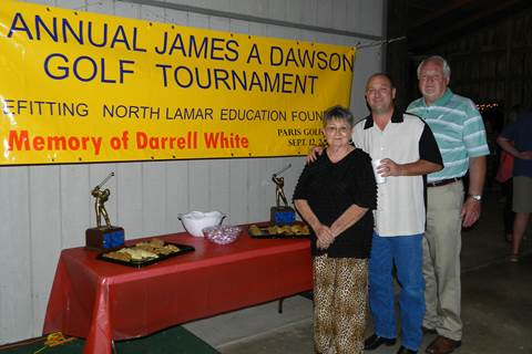 Sandra and Wade White, wife and son of the late Darrell White, stand with James A. Dawson at the Saturday Night Social and Auction following a golf tournament benefitting the North Lamar Education Foundation.