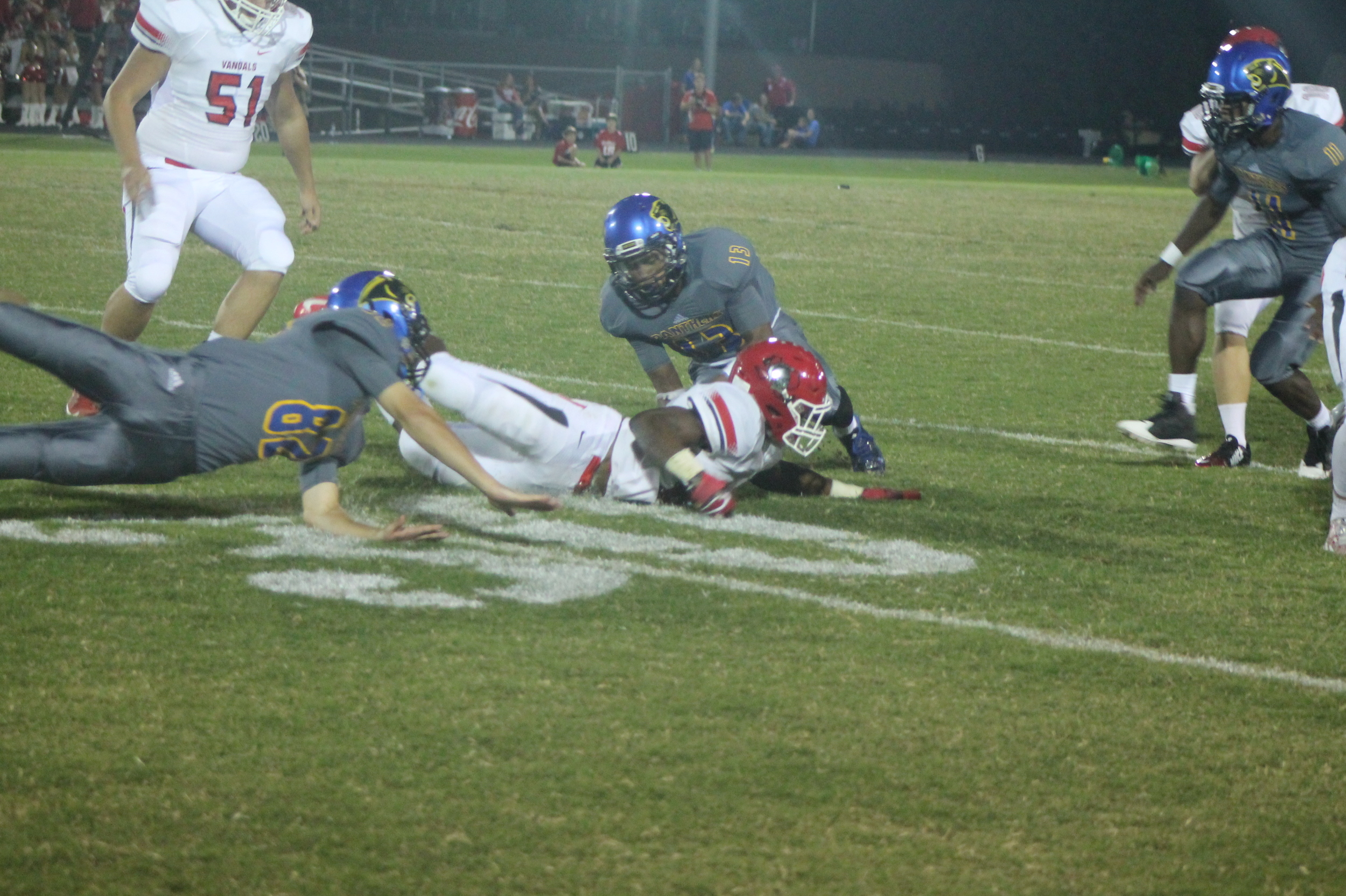 (Photo by Maddy Routon) Seybian Holt (13) recovers a fumbled kickoff while Jack Hill (82) goes diving in for the ball as well.