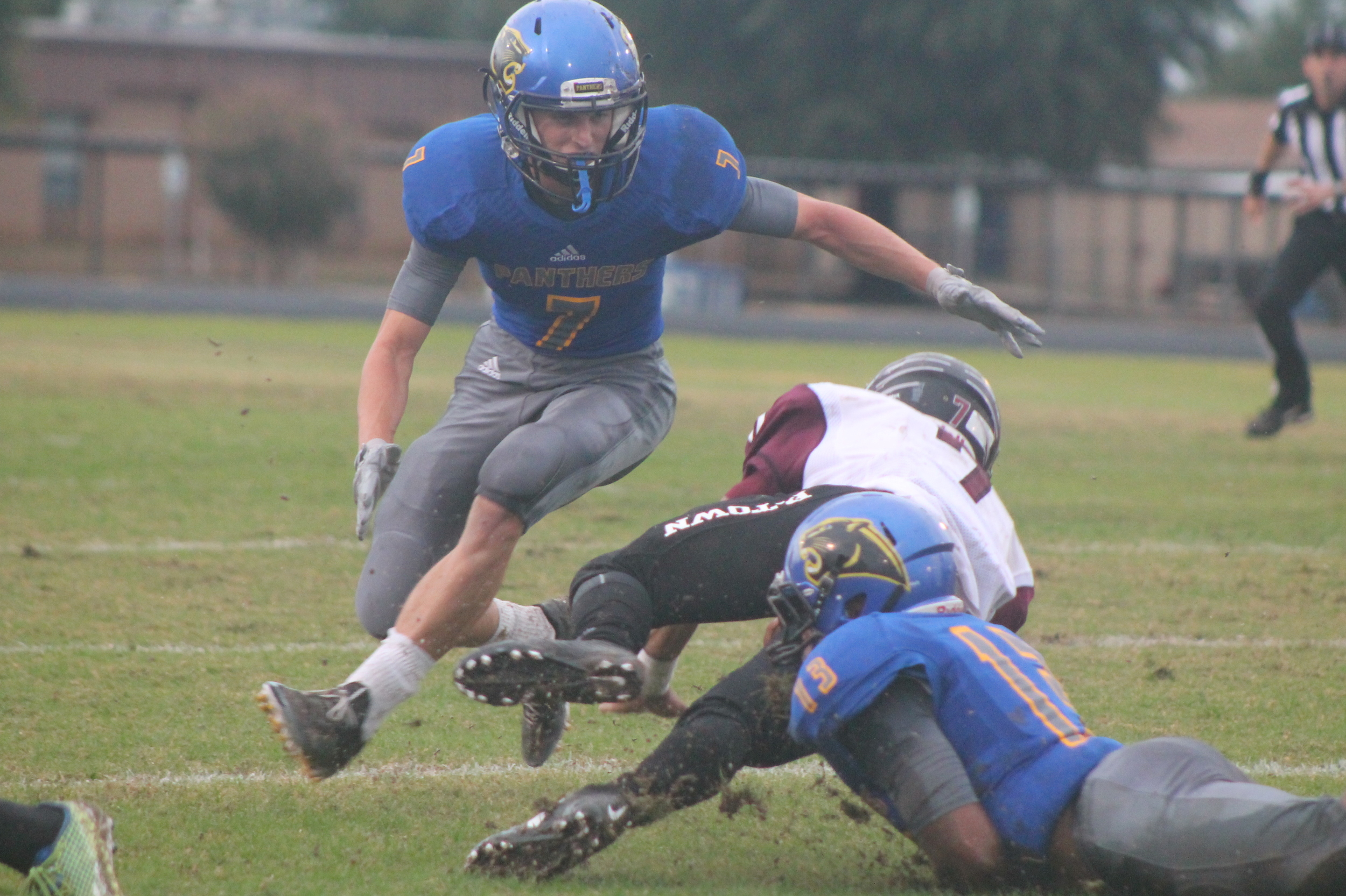(Photo by Maddy Routon) Seybian Holt (13) and Trey Scudder (7) Making a tackle on a Princeton player Friday night.