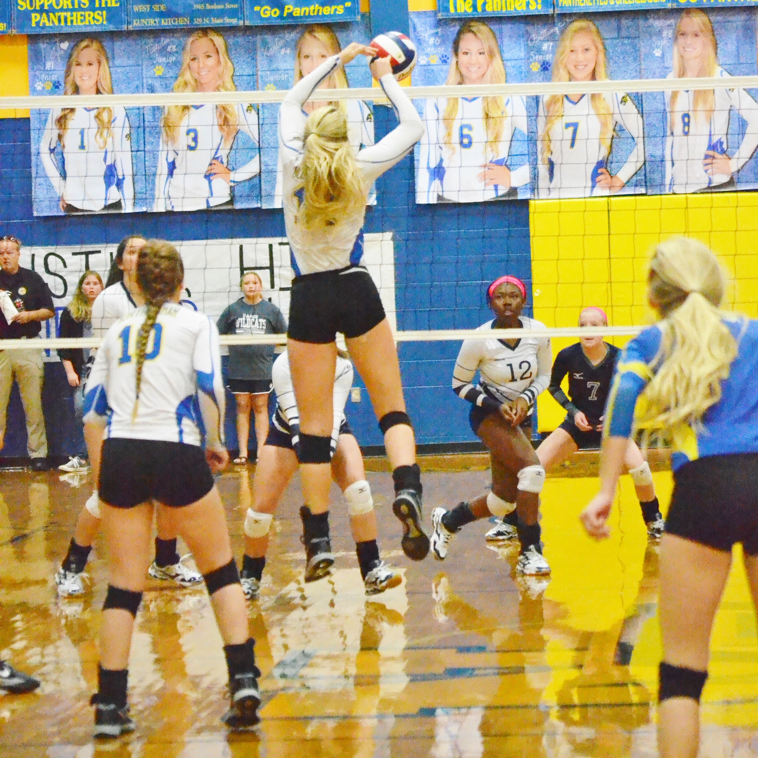 (Photo by Beverly White) Sydney Foy (14) hitting the ball at the net against Paris earlier this year while Bailee Nickerson (10) and Brittany Nichols (blue jersey) watch.