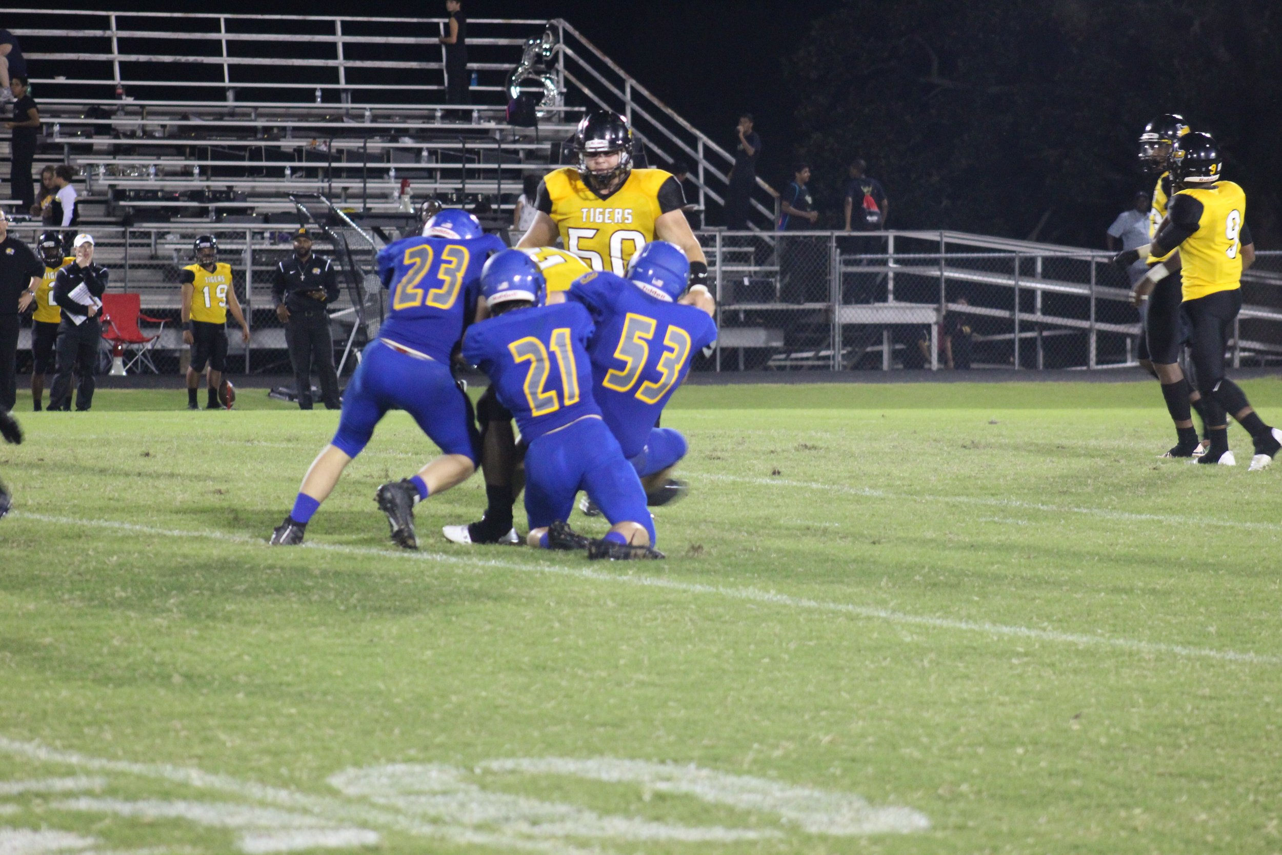 (Photo by Adam Routon) Austin Exum (23), Jeremiah Guenther (21) and Hunter Moore (53) bringing down a Mt. Pleasant player Friday night.
