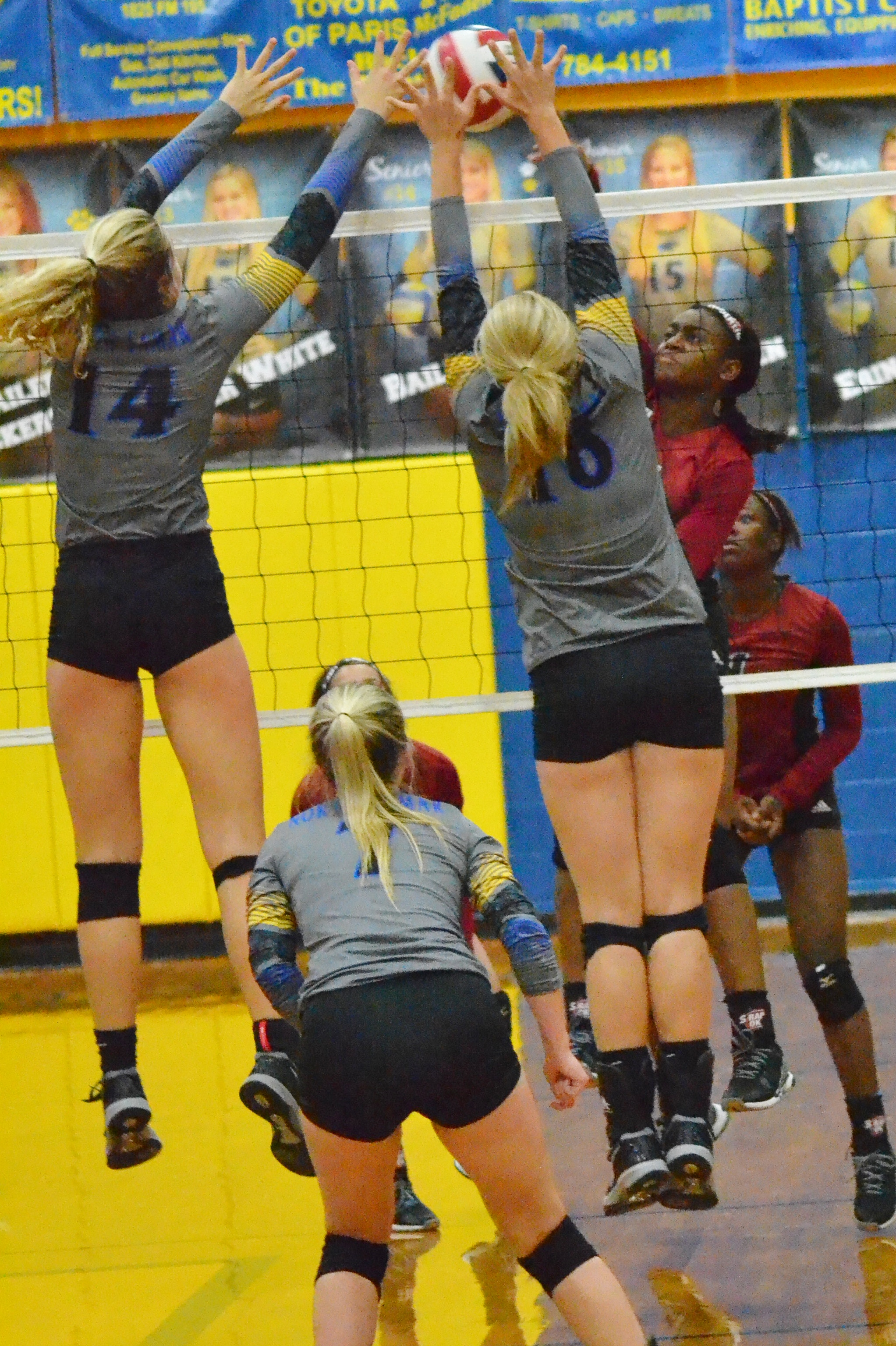 (Photo by Beverly White) Bailey Foy (14) and Erin Scholl (16) going up for a block against LE while Haley Porter (7) looks on.