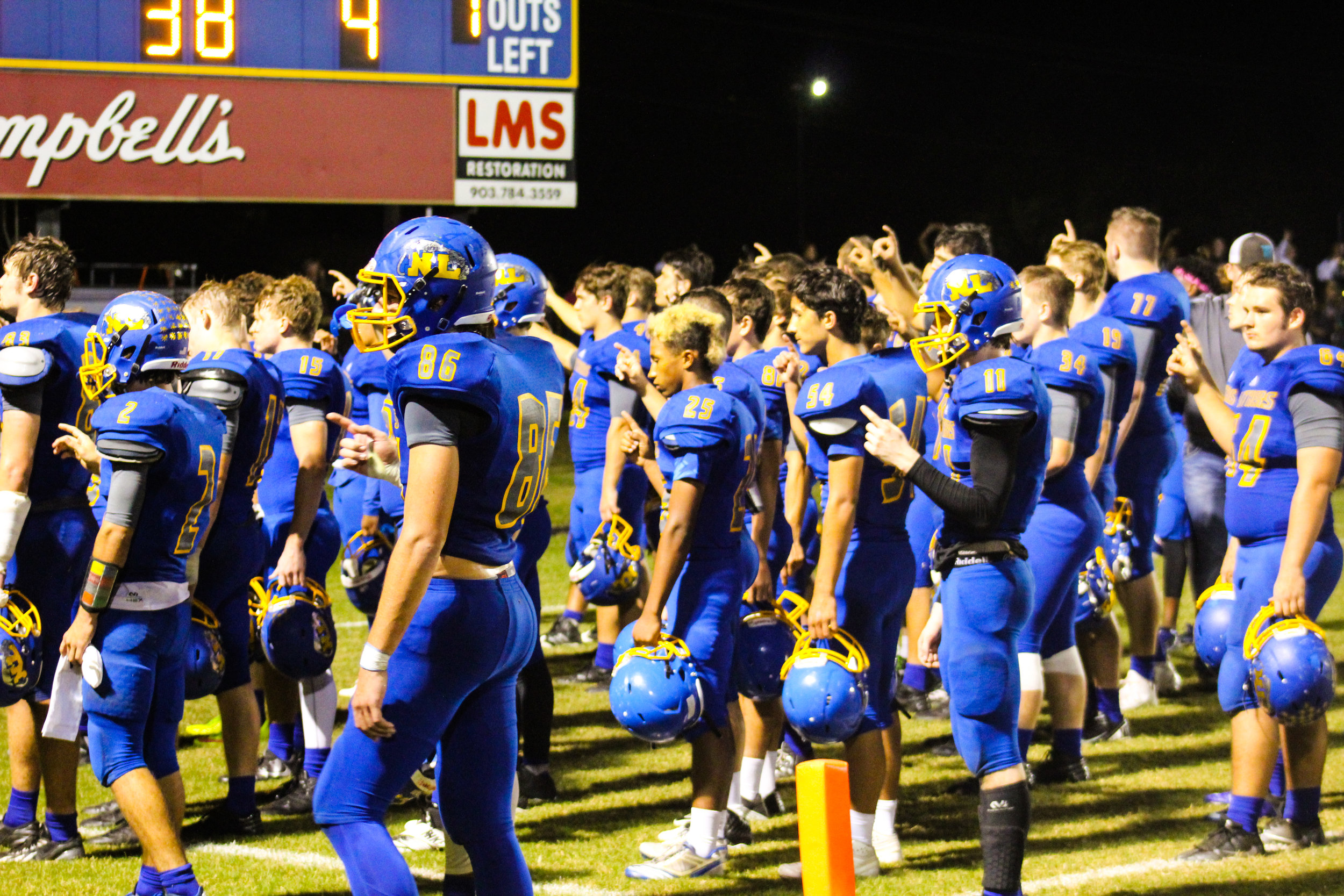 (Photo by Adam Routon) North Lamar listening to the band play the school song after Friday's game with Paris.