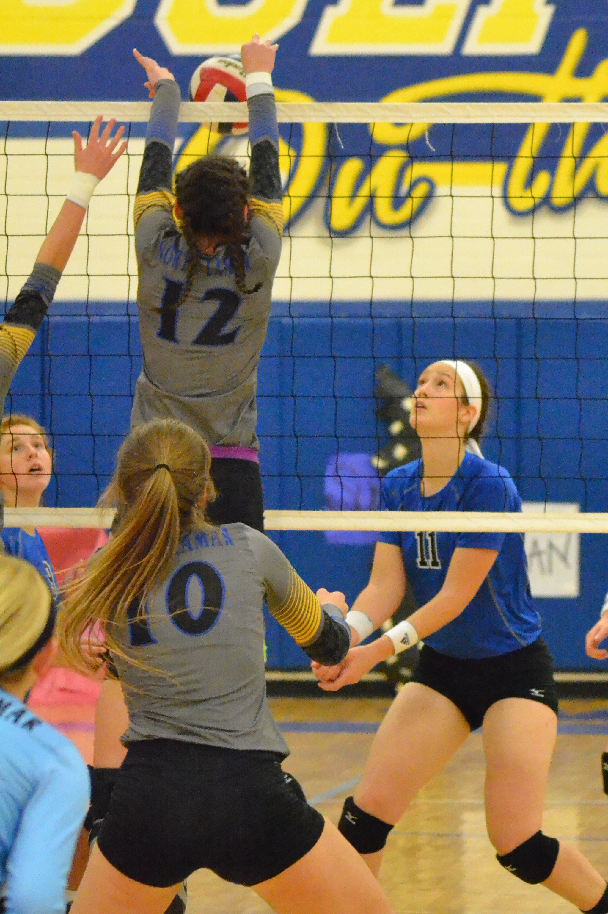 (Photo by Beverly White) McKenzie Mitchell (12) with a block against Emory Rains while Bailee Nickerson (10) watches.