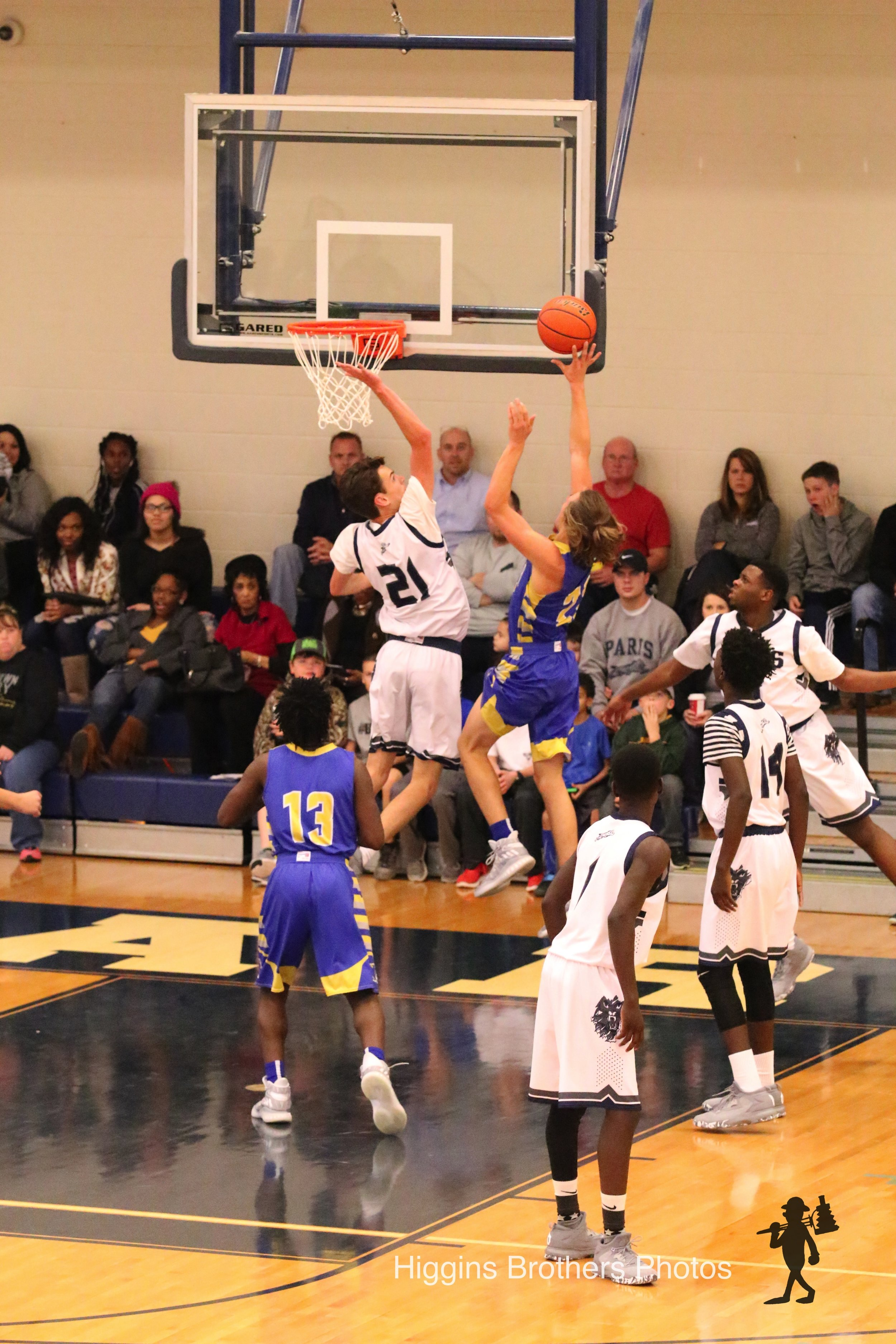 Photo by Bill Higgins: Sam Asay (21) going up for a shot while Menderiz Gray (13) watches.