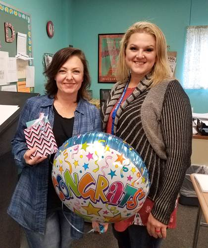 North Lamar High School English instructor LaDonna Davis receives a congratulatory gift and balloon from  Kortney Melton , NLISD ESL Coordinator, for passing her ESL certification.