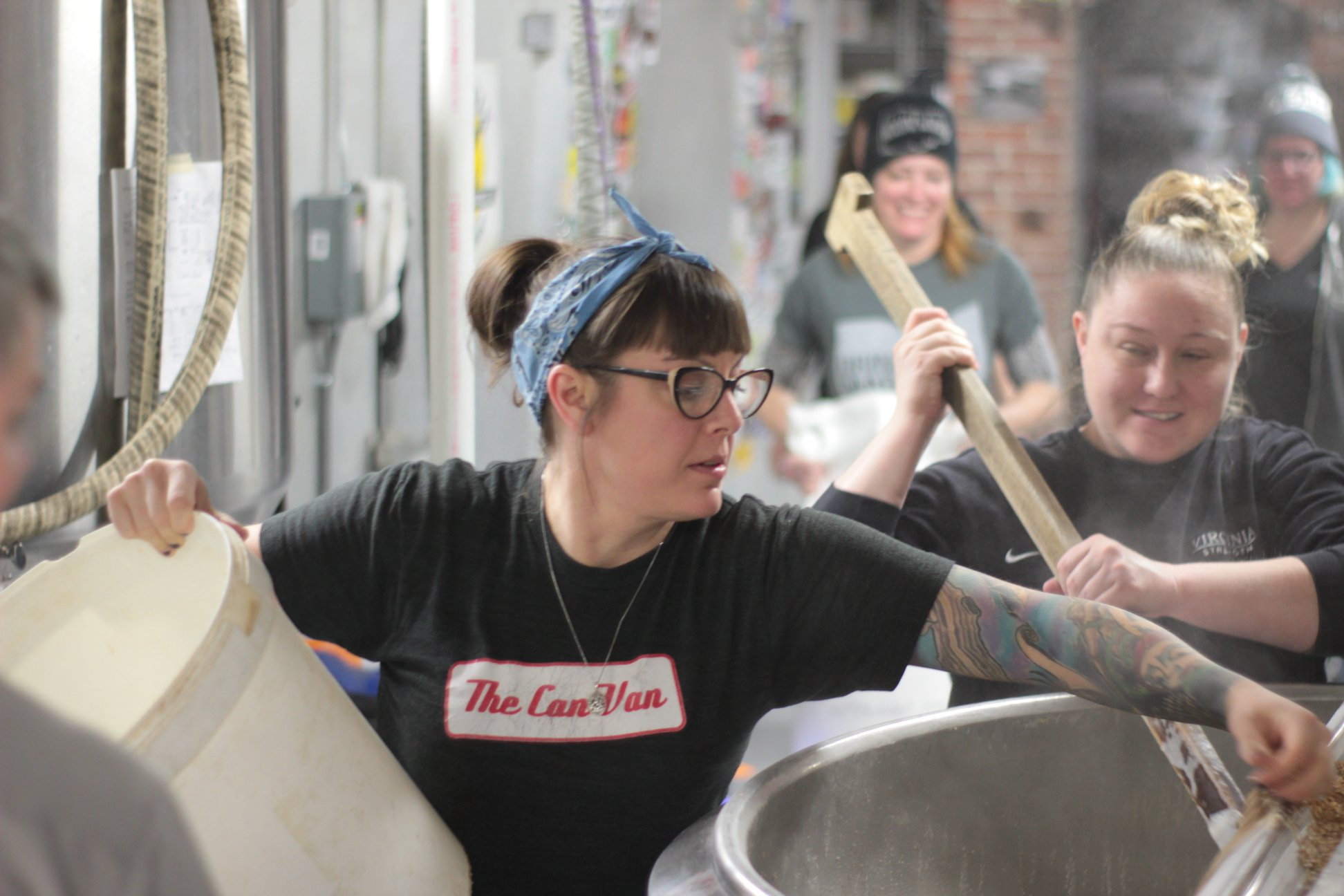 Nichole Endicott from Commonhouse Ales adding grain to the mash, and Michelle Warren from Multiple Brewing mashing in.