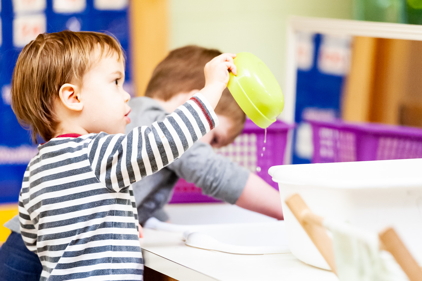 Our youngest children learn to care for their environment, including washing dishes.