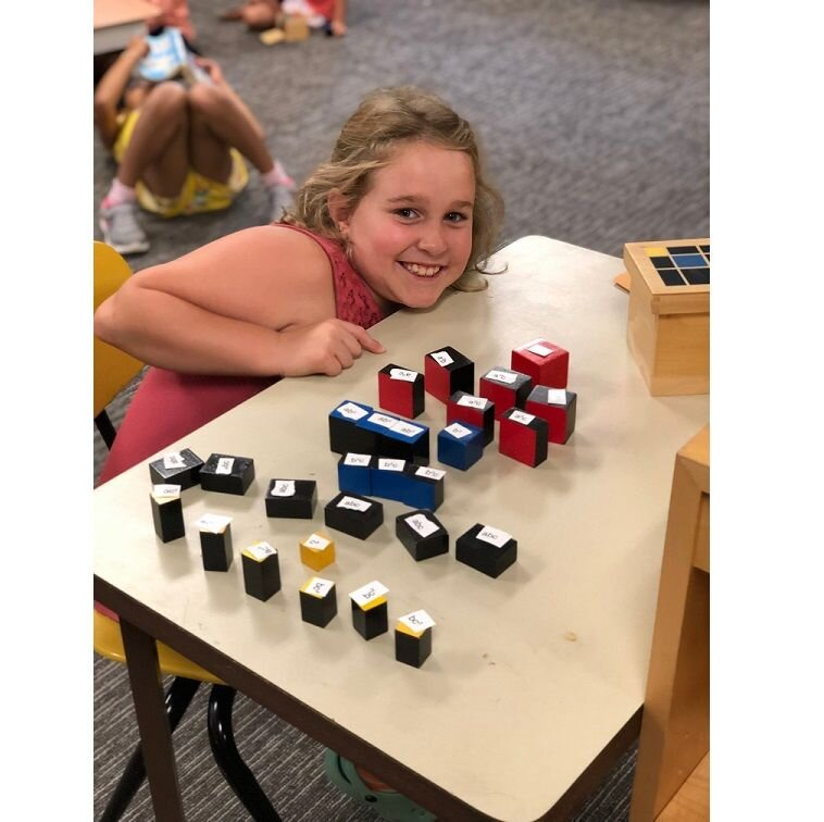 A third-grade-student labels the shapes of the Trinomial Cube to understand the mathematical equation that the material represents. She would have first used this as a 3-D puzzle in the Children's House, absorbing the information by repeatedly creating the cube.