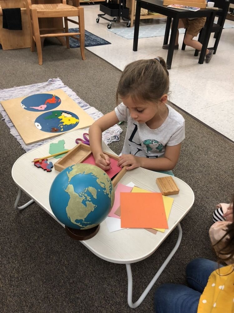 A five-year-old student works to create her own map of he world. She traces the continents onto colored paper and then uses an awl to perforate the paper. She will eventually punch out the shapes and adhere them to a large piece of paper to finish her work. Her final step will be writing the names of the continents.