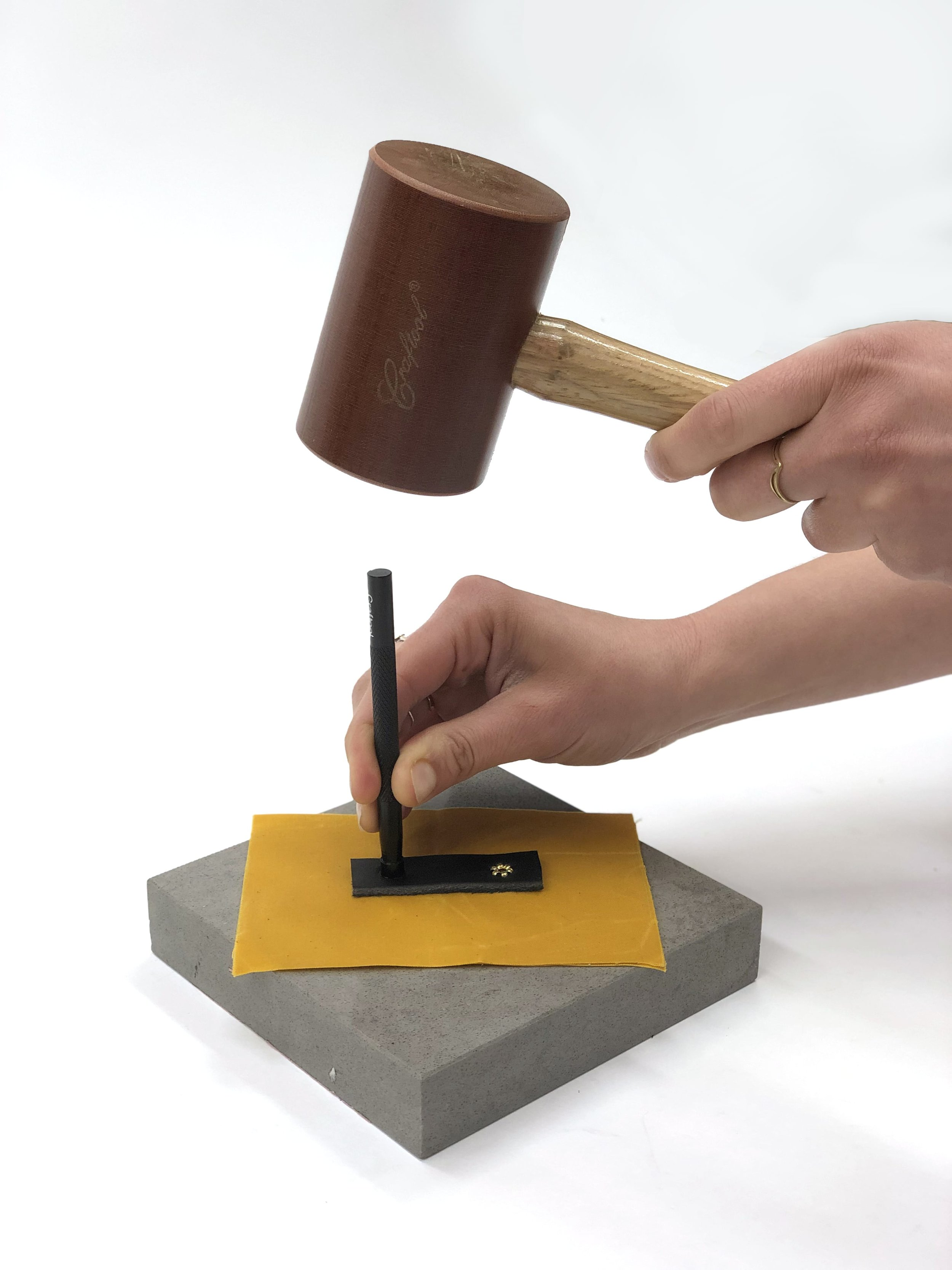 This is how a tubular rivet is set: with a tubular rivet peening tool and a mallet on a hard surface