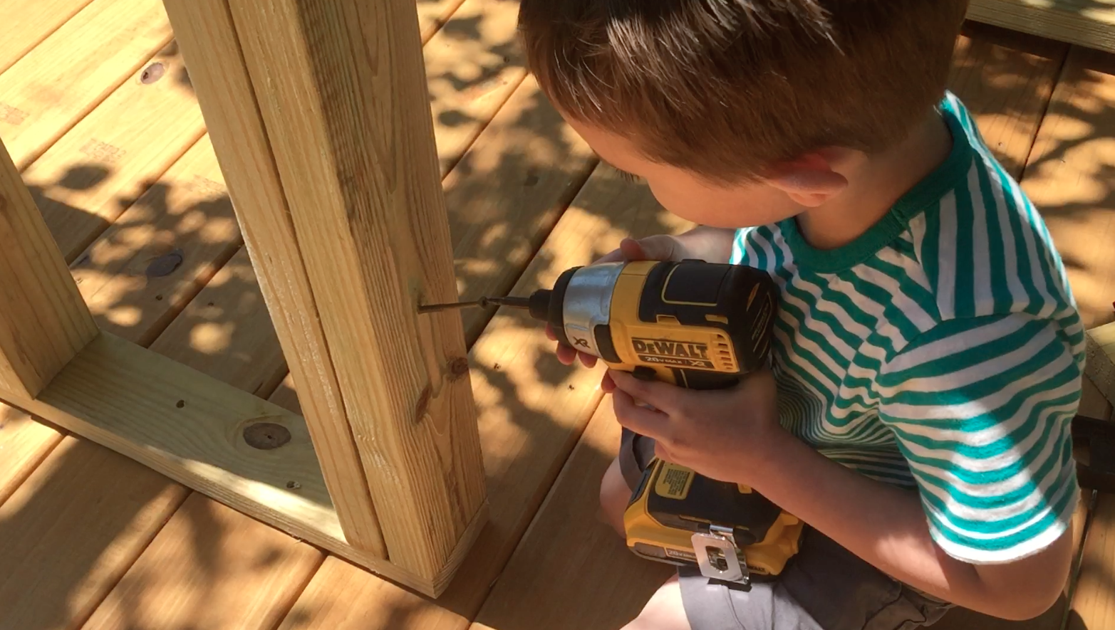 Ethan is putting in a screw to hold the door frame in place.