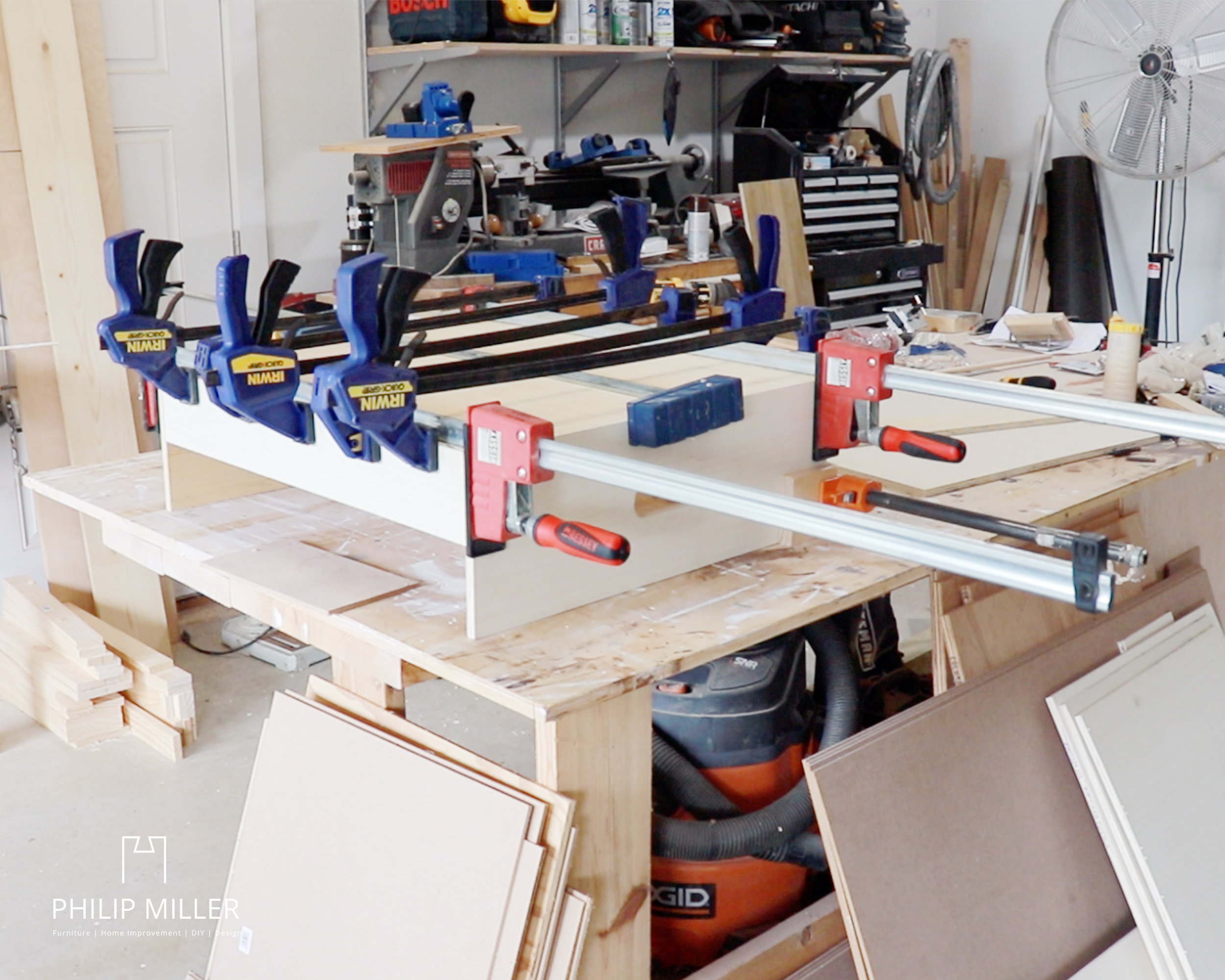 Clamping half inch plywood for a ring toss game using Irwin and Bessey clamps on a work bench