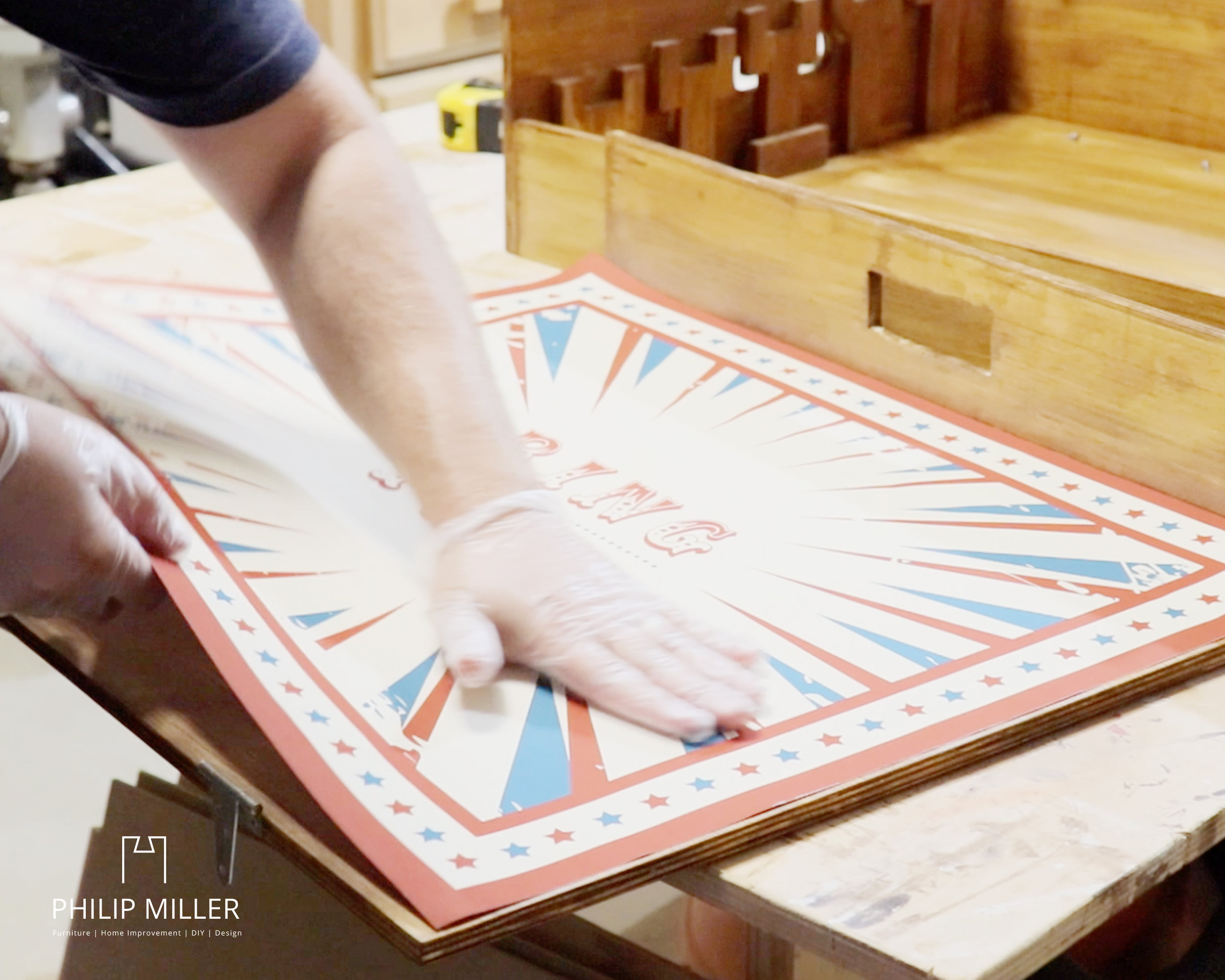 applying a ring toss graphic to wood in a work shop