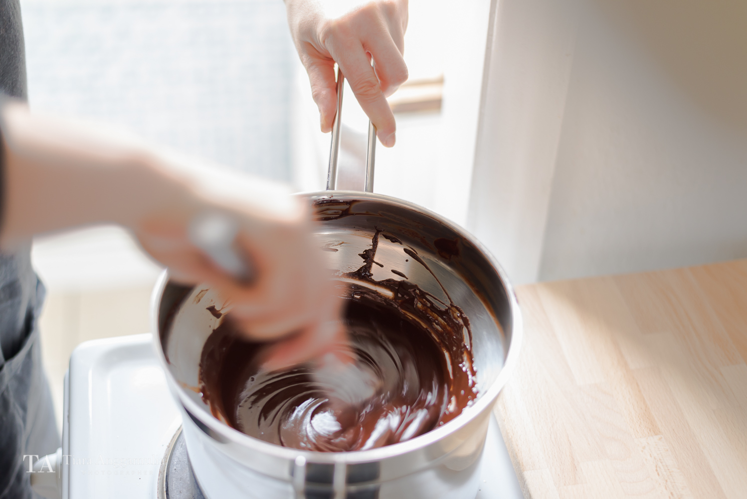 Stirring melted dark chocolate on a stove.