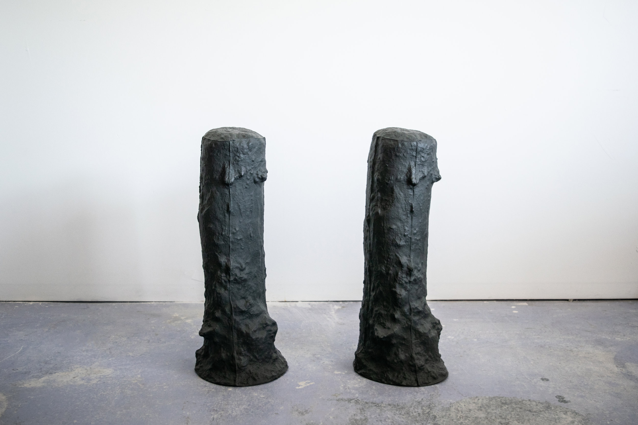"""terrain and territory , slip cast black porcelain with glazed interior 10"""" diameter x 28"""" tall. 2018   terrain and territory  focuses on the potent space of the fence post hole as a metaphor, and commentary against the current administrations determination to construct false narratives and divisions around issues regarding immigration, and """"us"""" and """"them"""" mentality. By pulling the subterranean space of the hole up and out of the ground as a hollow ceramic form, it shifts the functionality of the space as container, rather than divider, and placed; seeks to call into attention the skin of this often over looked space. The extension of a fences intention, to delineate, is further implied in the gallery by constructing an implied border between the two forms set in the space."""