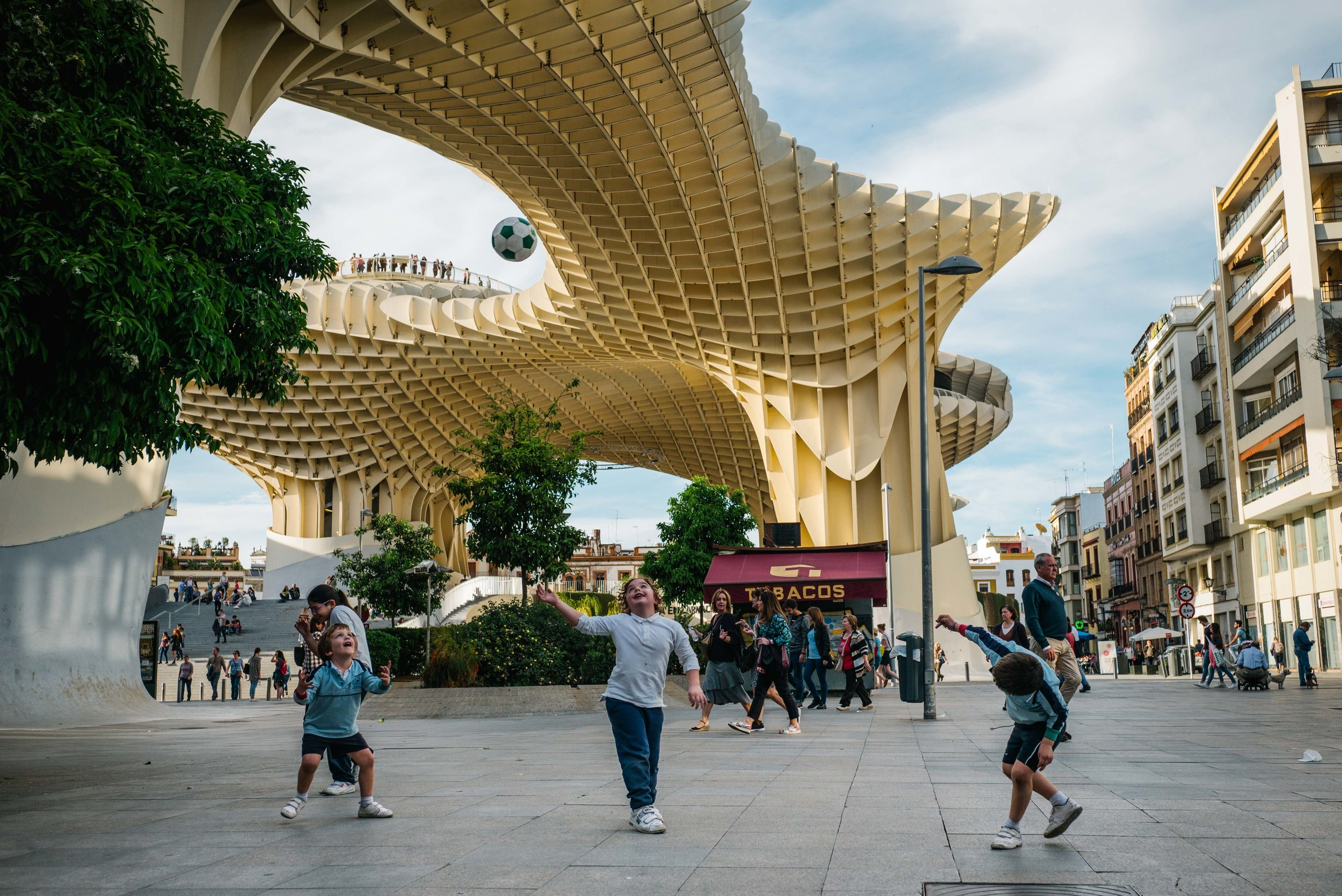 Three young boys play a game of 'piggy-in-the-middle' in front of the divisive Metropol Parasol, Seville. Spain. 2017.
