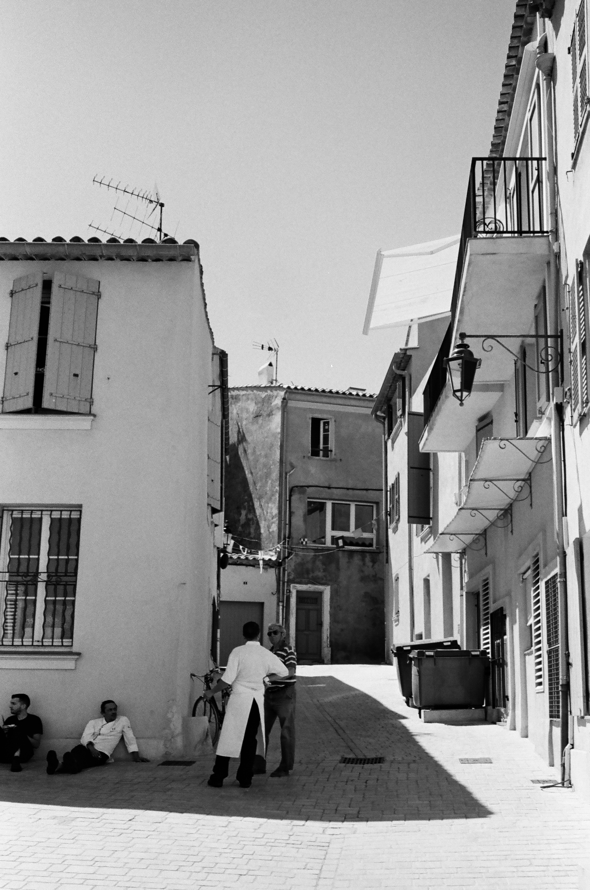 Restaurant workers take a break from the sun after a long lunch service, St. Tropez. France. 2016.
