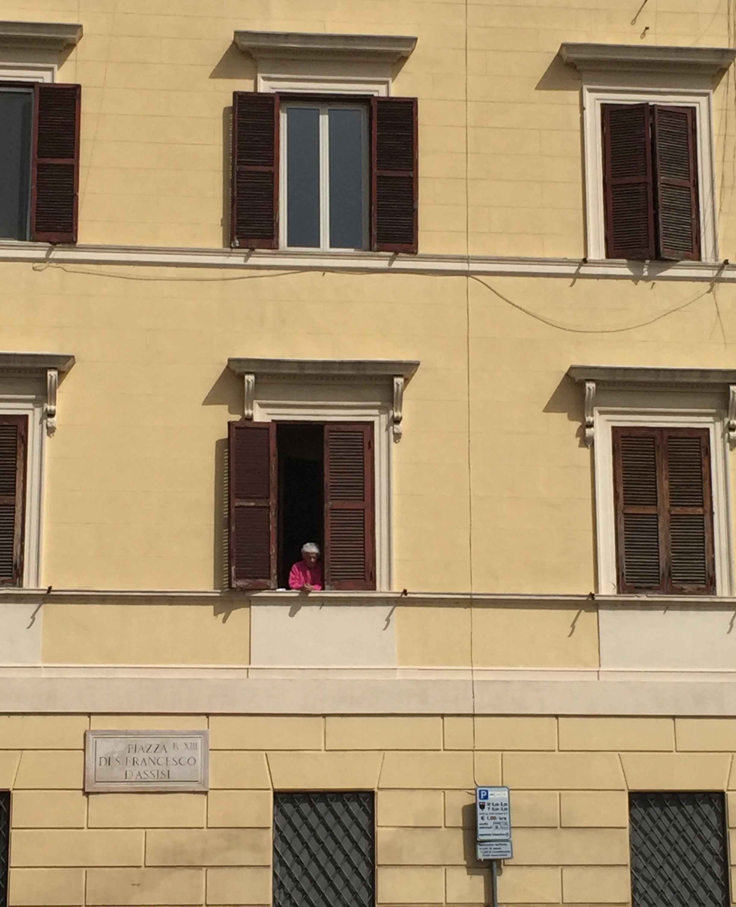 An elderly woman watches out over a Trastevere piazza. I love her pink shawl.
