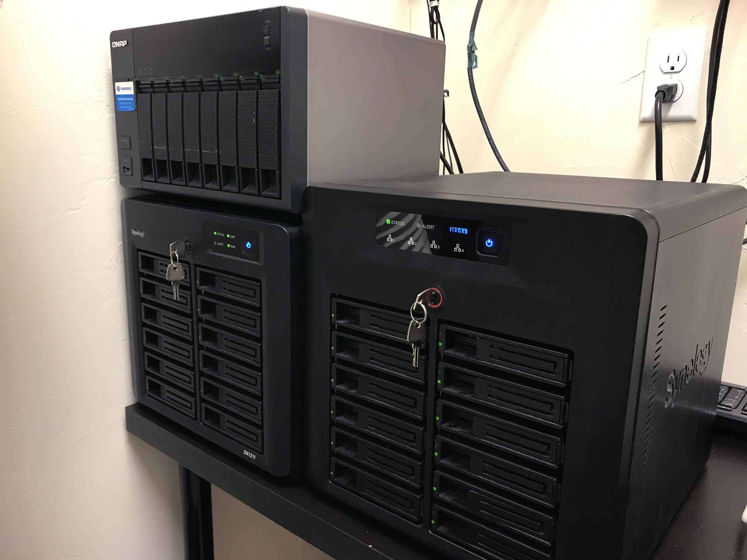 Network Attached Storage in-use at Mystery Box. NAS #1 is a Synology DS3612xs with DX1211 expansion unit, supporting up to 24 hard drives or SSDs (currently configured with 20 x 8TB HDD + 1 SSD with two disk redundancy for 144TB of Network Storage). NAS #2 is a QNAP TVS-871T populated with 8 x 6TB HDD with one disk redundancy. The Synology is used for archival storage while the QNAP is used for active RAW and Intermediate storage.