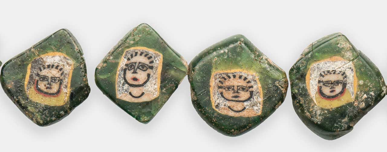 ENLARGED VIEWS OF FOUR NUBIAN FACE BEADS, from page 40; these very clear images show well the only representations of Medusa, as a Gorgon and as a woman. But in this case, the women are formed from Gorgon face canes, evident from the striations of their hair; numbering 8-9. The rectangular striations represent the writhing snakes of Gorgon.