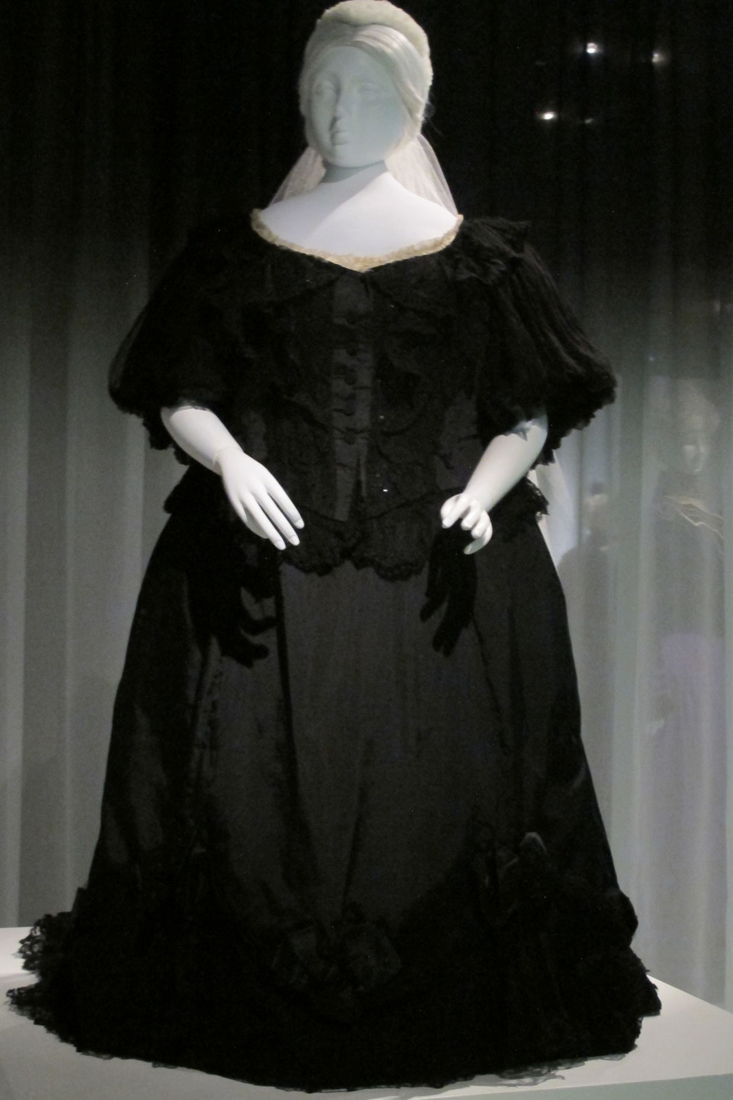 QUEEN VICTORIA MOURNING DRESS In black: silk taffeta, silk ribbon, silk lace, silk crepe, 1894-1895. The two views of Victoria's dress show the magisterial sweep of her gown, as well as the dispensing of forms of corseting that would bind and reshape her fulsome figure. Brooklyn Museum Costume Collection at the Metropolitan Museum of Art.