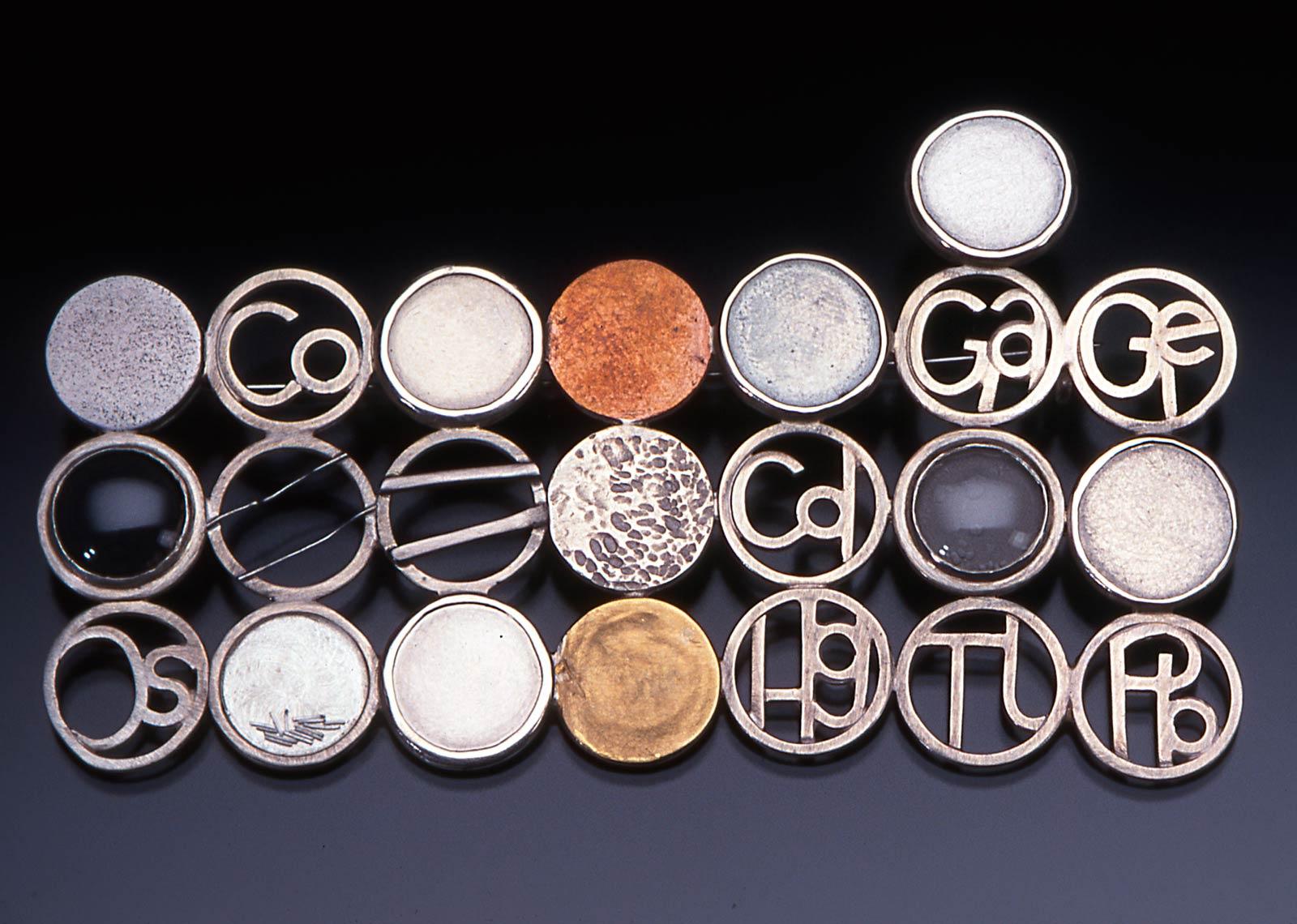 TRACE ELEMENTS 1 BROOCH of fabricated sterling silver set with aluminum, iron, nickel, copper, zinc, ruthenium, rhodium, palladium, silver, indium, tin, iridium, platinum, gold, 8.4 x 4.5 x 0.5 centimeters, 2000.