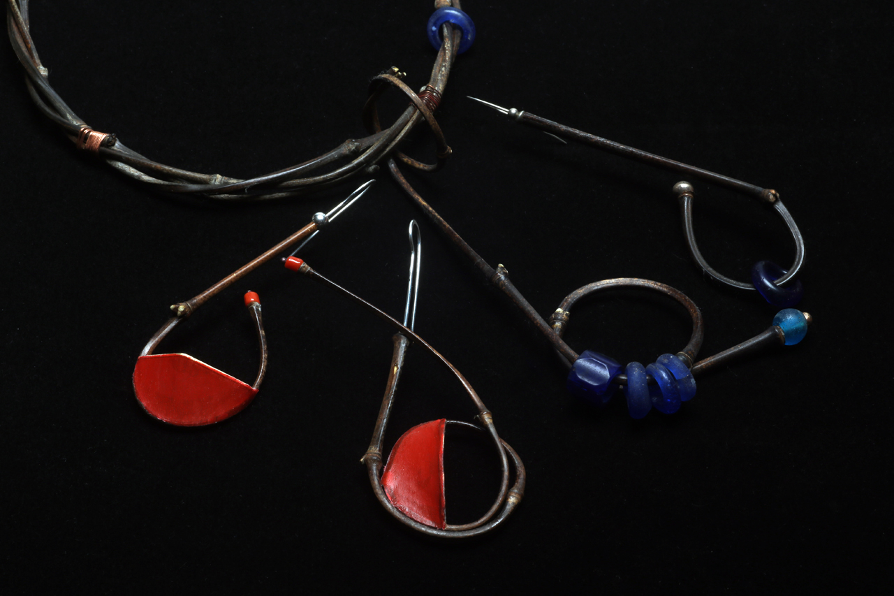CLOSEUP OF TIGHT RADIUS BEND PENDANT, COMPARED TO SINGLE AND DOUBLE TIGHT RADIUS BEND EARRINGS;  the one on the right is an older pair, made from bamboo harvested and dried for a long period, versus two Coverlite adorned ones on the left which are from freshly culled culms. The positioning of the wire matrix results in either horizontally or vertically oriented panels of red. Both have decorations of red precious coral and sterling silver beads, as well as hand-formed/forged silver earwires. The older example has vintage Bohemian glass, and Ethiopian silver beads for decorations. Earrings are 9.5 - 12.2 cm long.
