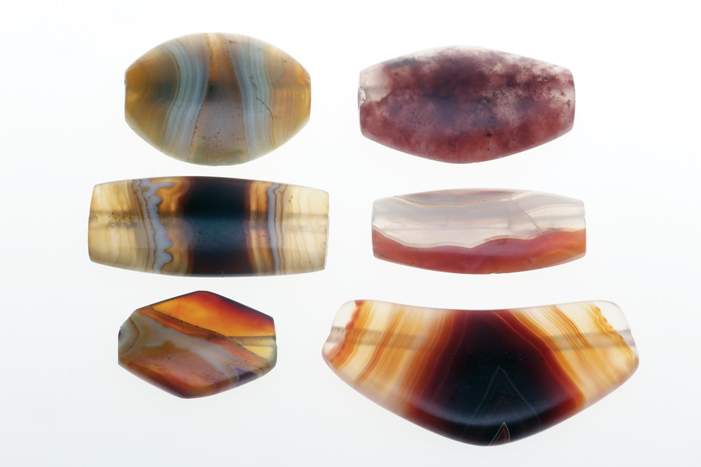 FOUR ANCIENT TABULAR/LENTICULAR HARD STONE BEADS FROM AFGHANISTAN AND TWO REPLICA AGATE BEADS; these carnelian and agate tabular beads are very similar to Mesopotamian third millennium beads, 2.8 - 3.5 centimeters long, 0.6 - 0.9 centimeters thick.  Courtesy of Anahita Gallery and J. Lafortune, 1978.  Two lowest beads are new replica tabular agate and leech beads from Iran and Cambay, 0.6 - 1.0 centimeters thick;  Courtesy of W. Seifried, 2006 and Beadazzled/Kamol, 1999.  Due to better lapidary equipment, especially drills, many replica beads are now thinner than the prototypes.  Photographs by Robert K. Liu/ Ornament ; shot with studio strobes, using softboxes   for both transillumination/reflected lighting or just reflective lighting when shooting on black Tufflock.
