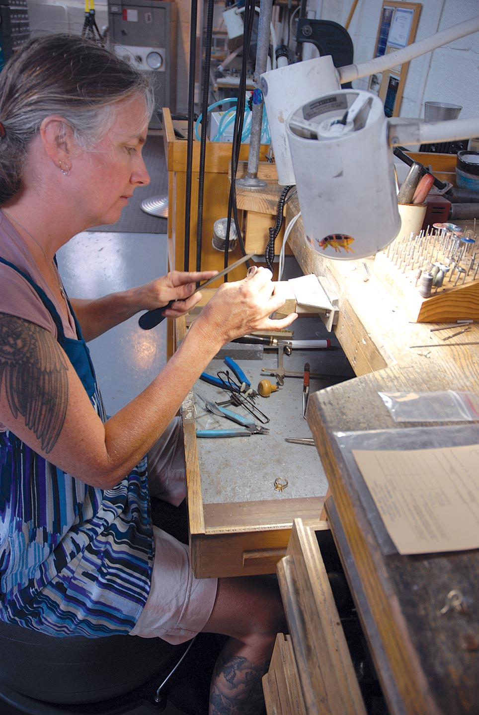 CAROL ROHMANN GREENE, Marraccini's assistant, working at her bench.